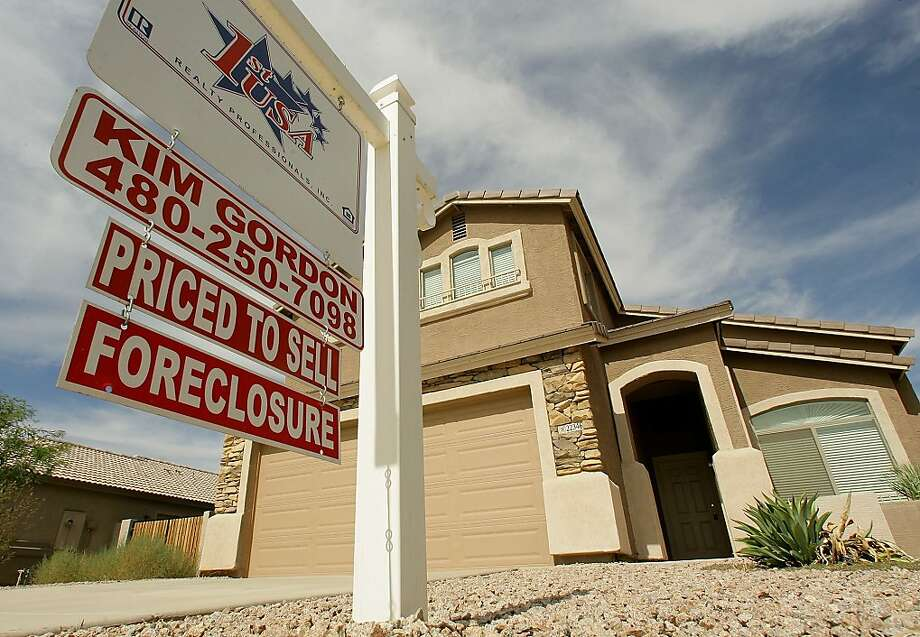 FILE - In this Sept. 26, 2007 file photo, a realty sign stands in front of one of the many homes that are in foreclosure in the Villages of Queen Creek in Queen Creek, Ariz. The number of U.S. homes repossessed by lenders fell to the lowest level in nearly six years last month amid a resurgent housing market and rising home prices, the latest evidence that the nation's foreclosure woes are easing, according to new data from foreclosure listing firm RealtyTrac Inc. (AP Photo/Ross D. Franklin, file) Photo: Ross D. Franklin, Associated Press