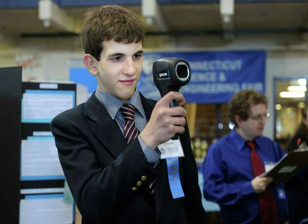 Paul Hansel, a freshman at Greenwich High School, uses a thermal imaging scanner to take the competition's temperature during judging for the Connecticut Science & Engineering Fair Thursday, Mar. 14, 2013 at Quinnipiac University in Hamden, Conn.  Hansel's project used the thermal scanner combined with a radio-controlled model plane to track deer tick populations. Photo: Autumn Driscoll / Connecticut Post