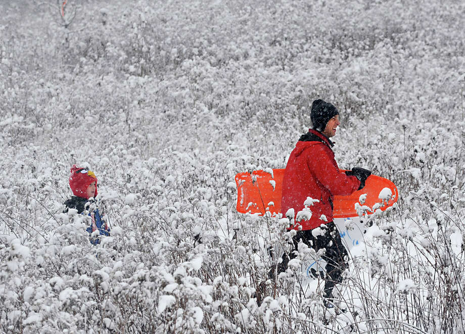 Mason Smolen, 6, of Guilderland starts the walk up the hill with his father Tom Smolen after sledding into the weeds at the Tawasentha Park Winter Recreation Area during the Capital Region's first snow storm of the season on Thursday Dec. 27, 2012 in Guilderland, N.Y. (Lori Van Buren / Times Union) Photo: Lori Van Buren / 00020593A