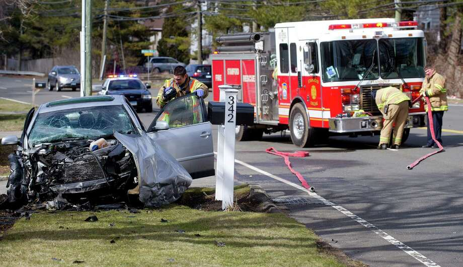 A vehicle sits on the shoulder of Long Ridge Road after crashing into a stone wall on a property at 342 Long Ridge Road on Thursday, March 14, 2013. Photo: Lindsay Perry / Stamford Advocate