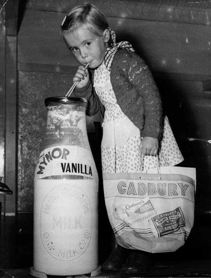 A young girl drinking from an outsize bottle of milk at the 1950 Royal Easter Show carrying a bag advertising Cadbury's chocolate. Photo: Hulton Archive, / / Hulton Archive