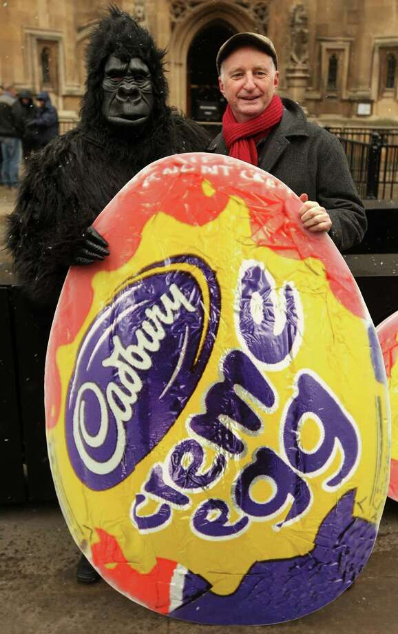 A man dressed as a gorilla and singer Billy Bragg pose with a poster of a giant Cadbury creme egg as they protest against the potential sale of Cadbury to Kraft Foods outside the Houses of Parliament on Dec. 16, 2009 in London. American food producer Kraft made a hostile bid for Cadbury before an agreement was reached. In the U.S. however, Cadbury products are made by Hershey. Photo: Oli Scarff, / / 2009 Getty Images