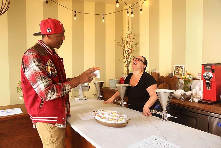 Customer Tony Donnell (left) samples a creation made by Doughnut Dolly owner Hannah Hoffman. Photo: Liz Hafalia, The Chronicle