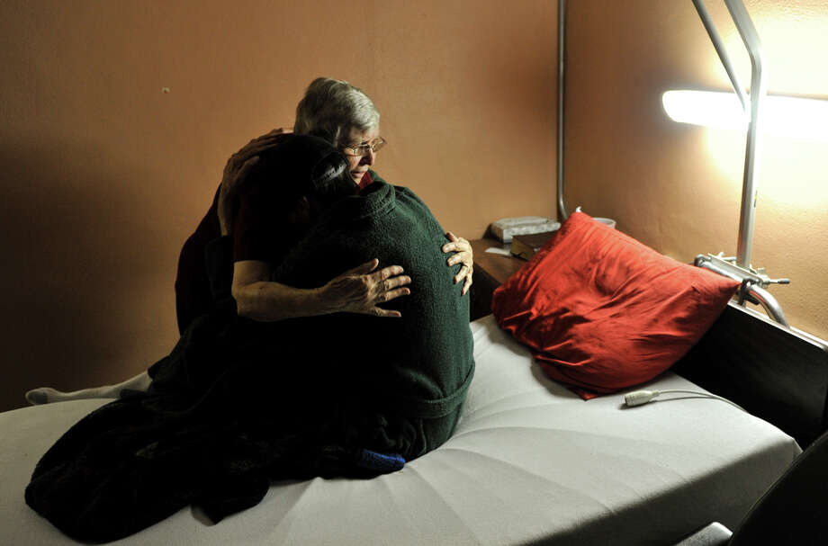 Sister Mary Muldowney hugs patient Duke Brown at the San Antonio Aids Foundation during one of her twice-weekly visits recently. Photo: Robin Jerstad