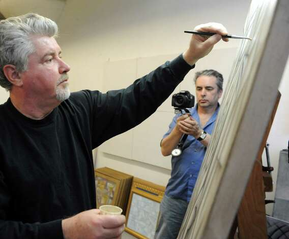 Markus Innocenti films Greenwich artist Paul Larson painting at the Loft Artists Association in Stamford on Wednesday, February 20, 2013. The video, which will largely be filmed in Stamford, will also feature an original song written and performed by Stamford resident Kathy Muir. Photo: Lindsay Perry / Stamford Advocate