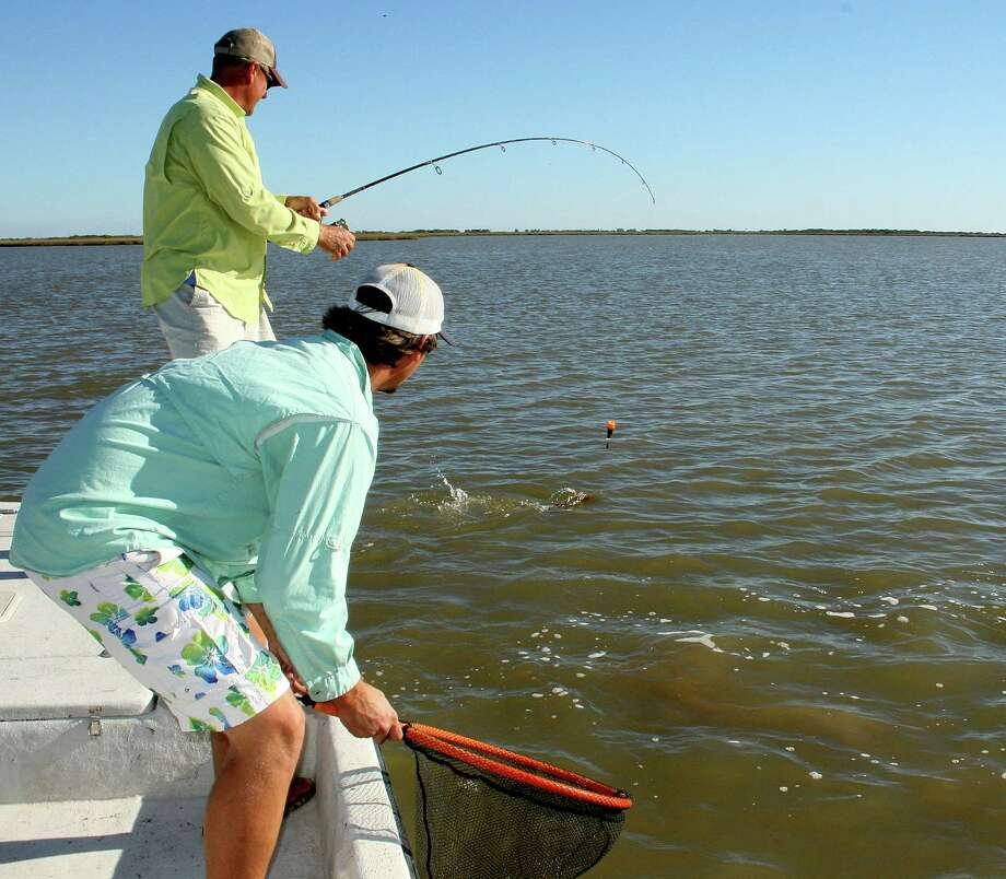 As Blain Talasek waits with a landing net, guide Mark Talasek wrestles a 25-inch redfish. Photo: Shannon Tompkins