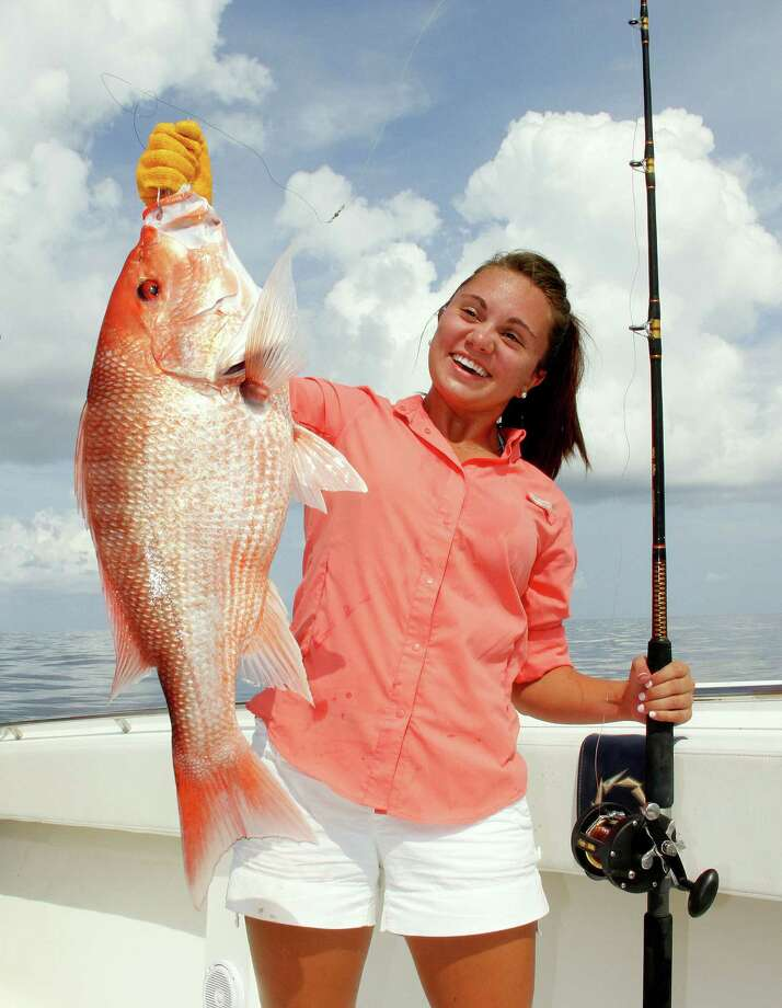 "Gloves specificaly designed for handling fish, such as the classic ""orange gloves""  angler Sara Dougas uses to protect her hand while hoisting this red snapper, reduce chances of injuries from fish fins, teeth and gill plates.  Houston Chronicle photo by Shannon Tompkins Photo: Shannon Tompkins"