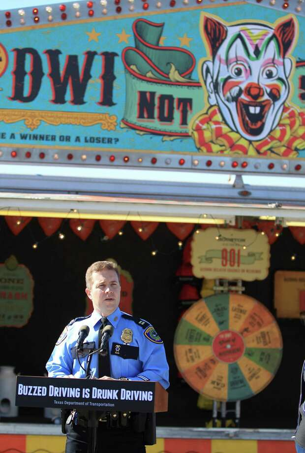 "HPD Captain L. Baimbridge speaks to the media during TxDOT's Buzzed Driving Campaign event in the parking lot of Rebels Honky Tonk in Houston.  TxDOT has repurposed a classic carnival game trailer into the ""DWI Not So Fun House"" which invites entertainment district revelers to play carnival games, spin a wheel of misfortune or try to steer a driving simulator, all while simulating the experience of being drunk. Photo: Karen Warren, Houston Chronicle / © 2013 Houston Chronicle"