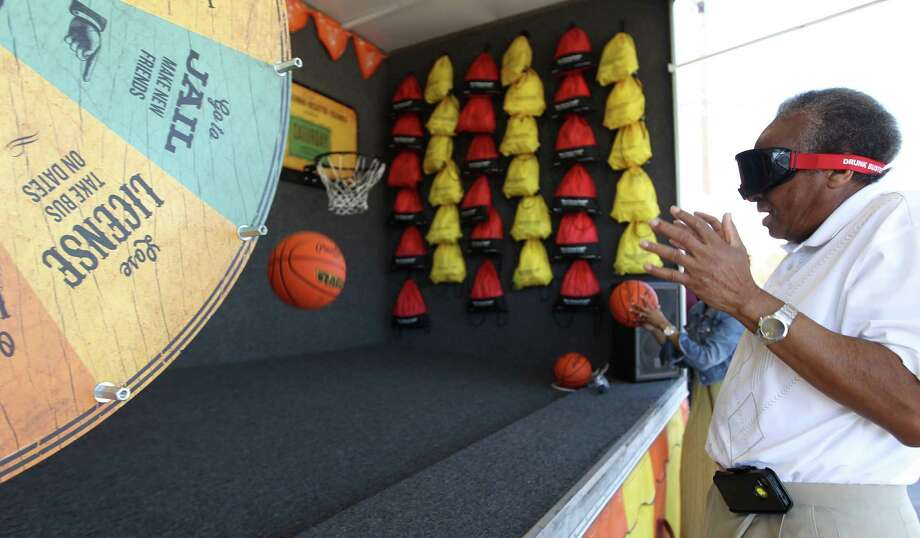 "Shelby Samuels reacts as he plays basketball with Fatal Vision goggles on at the ""DWI Not So Fun House"" in the during TxDOT's Buzzed Driving Campaign event. Photo: Karen Warren, Houston Chronicle / © 2013 Houston Chronicle"