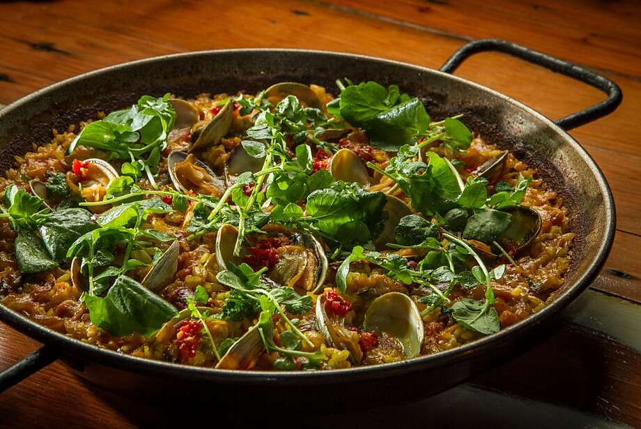 The paella is served with slightly chewy Spanish bomba rice, whole cippolini onions, chunks of rabbit and salsa Diablo. Photo: John Storey, Special To The Chronicle
