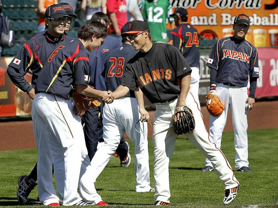 Giants infielder Kensuke Tanaka greets his countrymen from Japan's national team before playing them in an exhibition. Photo: Michael Macor, The Chronicle