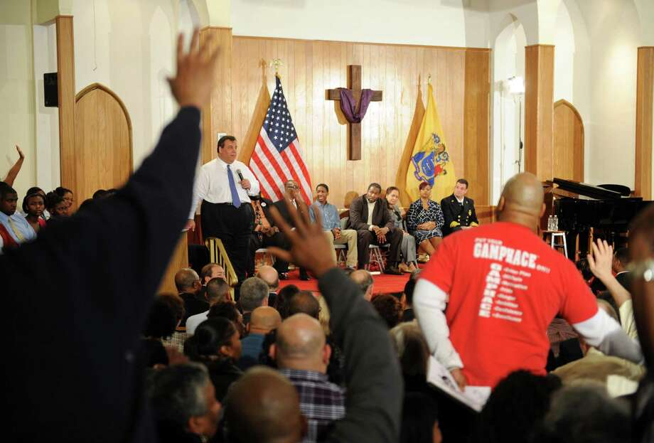 In this photo taken Tuesday, March 12, 2013Local residents try to get the attention of Gov. Chris Christie during a town hall meeting at St. Luke Baptist Church in Paterson, N.J. over 700 people attended the event. (AP Photo/The Record of Bergen County, Tyson Trish) Photo: Tyson Trish