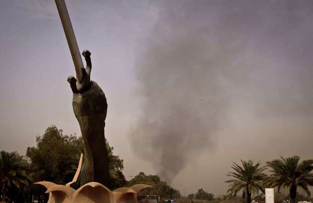 Black smoke from a car bomb attack is seen from the the Crossed Words monument in Baghdad, Iraq, Thursday, March, 14, 2013. A string of explosions tore through central Baghdad within minutes of each other on Thursday, followed by what appeared to be a coordinated assault by gunmen who battled security forces in the Iraqi capital, according to officials. Authorities say several people have been killed. (AP Photo/Maya Alleruzzo) Photo: Maya Alleruzzo