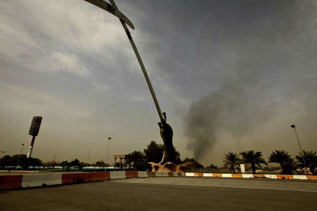 Black smoke from a car bomb attack is seen from the the Crossed Words monument in Baghad, Iraq Thursday, March, 14, 2013. A string of explosions tore through central Baghdad within minutes of each other on Thursday, followed by what appeared to be a coordinated assault by gunmen who battled security forces in the Iraqi capital, according to officials. Authorities say several people have been killed. (AP Photo/Maya Alleruzzo) Photo: Maya Alleruzzo