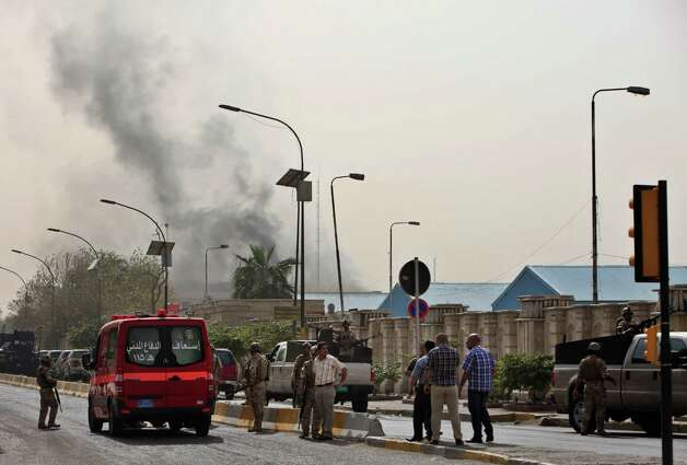 Black smoke from a car bomb attack is seen in Baghdad, Iraq, Thursday, March, 14, 2013. A string of explosions tore through central Baghdad within minutes of each other on Thursday, followed by what appeared to be a coordinated assault by gunmen who battled security forces in the Iraqi capital, according to officials. Authorities say more than a dozen  have been killed. (AP Photo/Karim Kadim) Photo: Karim Kadim