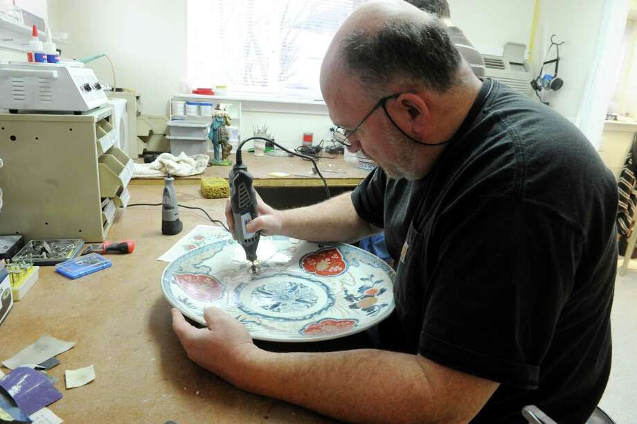 Morty Bachar, co-owner, of Lakeside Pottery, works on the broken parts of the china platter soon looking perfect, in Stamford, Conn., Monday, March 11, 2013. He repairs ceramics, pottery or a stone sculpture at his shop which brings a national clientele. Photo: Helen Neafsey / Greenwich Time