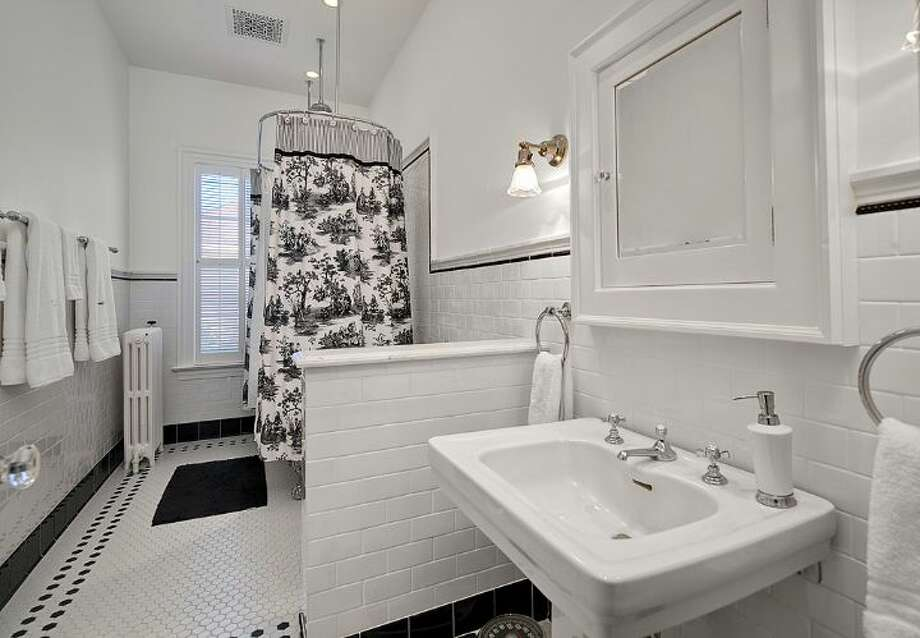 Bathroom of 3008 Webster Point Road N.E. The 7,404-square-foot mansion, built in 1910, has seven bedrooms, 4.5 bathrooms, a sunroom, a den, a game room, a media room, leaded glass, massive moldings, sport and tennis courts, a dock with a boat lift and views of Lake Washington and the Cascade Mountains on a 0.41-acre lot. It's listed for $4.75 million. Photo: Courtesy Kim Knowles And Tom Maider/Windermere Real Estate