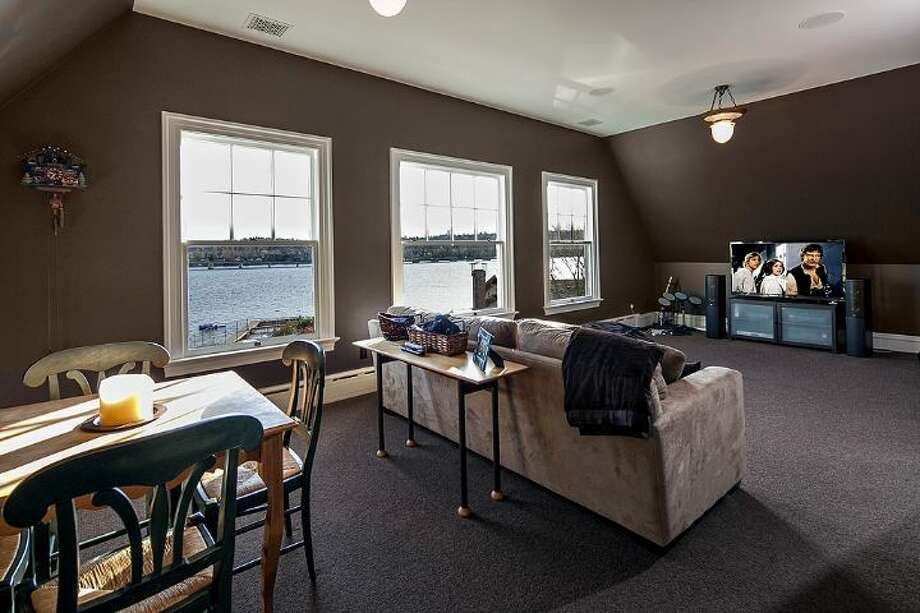 Media room of 3008 Webster Point Road N.E. The 7,404-square-foot mansion, built in 1910, has seven bedrooms, 4.5 bathrooms, a sunroom, a den, a game room, leaded glass, massive moldings, sport and tennis courts, a dock with a boat lift and views of Lake Washington and the Cascade Mountains on a 0.41-acre lot. It's listed for $4.75 million. Photo: Courtesy Kim Knowles And Tom Maider/Windermere Real Estate