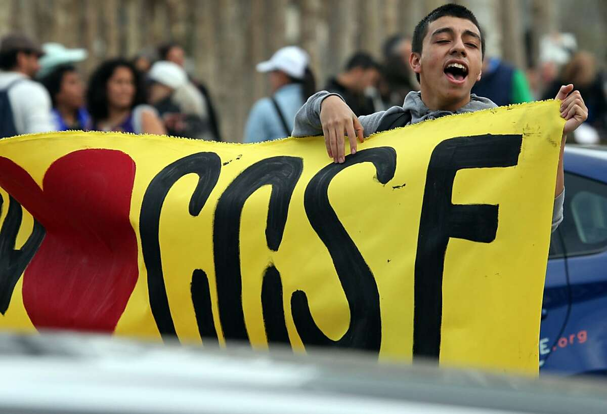 Samuel Rangel a student at City College of San Francisco yells at motorist to honk in support of the college.