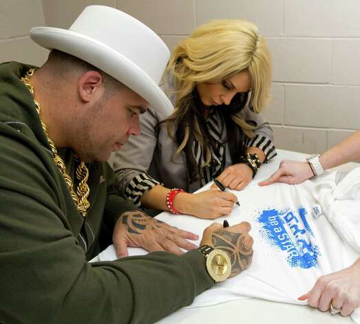 "Brodus Clay, left, and ""Diva"" Kaitlyn, right, sign autographs for young fans after speaking during an anti-bullying event at Westover Elementary School on Thursday, March 14, 2013. Photo: Lindsay Perry / Stamford Advocate"