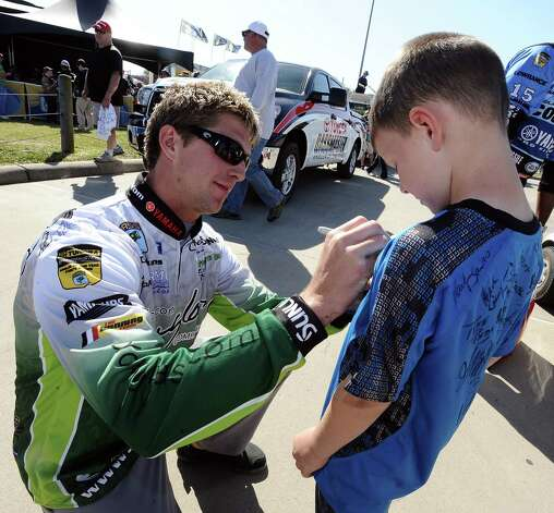 Angler Chad Pipkens, left, signs seven year old Kyle McQueen's jersey after his weigh in for the 2013 Bassmaster Elite Series Sabine River Challenge on Thursday, March 14, 2013. Photo taken: Randy Edwards/The Enterprise Photo: Randy Edwards