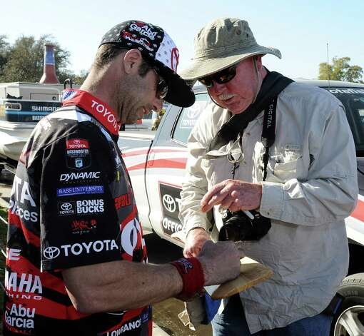 Angler Mike Iaconelli signs some memorabilia for Buddy Ellis after his weigh in at the 2013 Bassmaster Elite Series Sabine River Challenge on Thursday, March 14, 2013. Photo taken: Randy Edwards/The Enterprise Photo: Randy Edwards