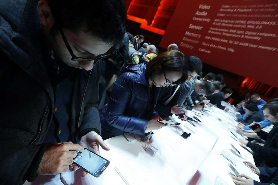 Attendees try out the new Samsung Galaxy S 4 at the Samsung Unpacked event at Radio City Music Hall. Photo: Jason DeCrow, Associated Press