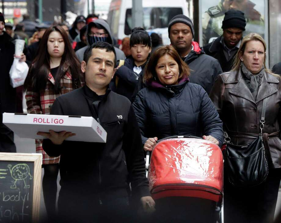 People walk through New York's Financial District,  Thursday, March 14, 2013.  New statistics show more people moved into New York City than out of it last year for the first time in more than 60 years. (AP Photo/Richard Drew) Photo: Richard Drew