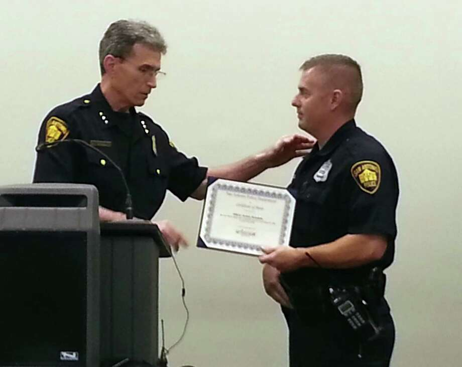 Officer Jeremy Swindells receives a certificate of merit from Chief William McManus for helping save a family from a fire. Photo: Michelle Mondo / San Antonio Express-News