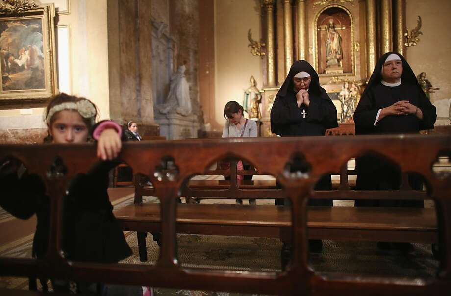 Nuns worship as a girl looks on in the Metropolitan Cathedral during Mass on the day after Pope Francis was elected at the conclave on March 14, 2013 in Buenos Aires, Argentina. Francis was the archbishop of Buenos Aires and is the first Pope to hail from South America.  Photo: Mario Tama, Getty Images
