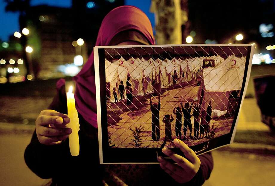 "A protester holds a poster with partial Arabic that reads, ""rescue us,"" during the candlelit vigil, marking the second anniversary of the Syrian revolution, in Cairo, Egypt, Thursday, March 14, 2013.  Photo: Nasser Nasser, Associated Press"