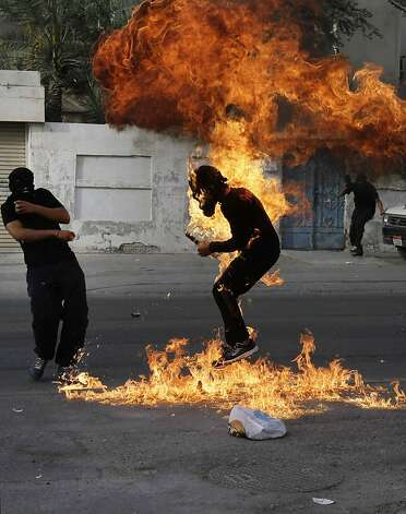 "A Bahraini anti-government protester is engulfed in flames when a shot fired by riot police hit the petrol bomb in his hand that he was preparing to throw during clashes in Sanabis, Bahrain, Thursday, March 14, 2013. Protests and clashes erupted in opposition areas nationwide Thursday with government opponents observing a ""Dignity Strike"" _ blocking roads, closing shops, protesting and staying home from work and school _ called by the more radical February 14 youth group.  Photo: Hasan Jamali, Associated Press"