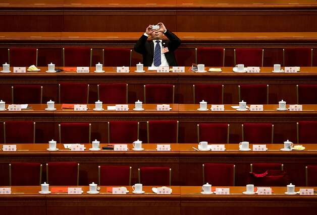 A delegate uses a smartphone to take pictures before a plenary session of the National People's Congress held at the Great Hall of the People in Beijing Thursday, March 14, 2013. China's new leader Xi Jinping capped his rise Thursday by adding the largely ceremonial title of president, though he will need cautious maneuvering to consolidate his power and build support from a public that is increasingly clamoring for change.  Photo: Andy Wong, Associated Press