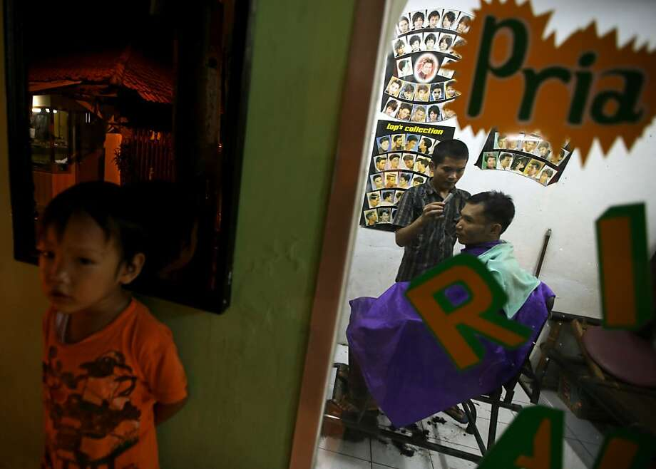 "An Indonesian man has his hair cut as a boy stands near by at a barber shop in Jakarta, Indonesia, Thursday, March 14, 2013. The writing on the window reads ""Men's barber.""  Photo: Dita Alangkara, Associated Press"