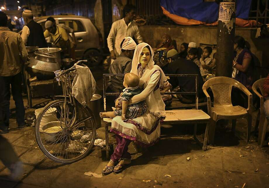 An Indian Muslim woman holds her child as she waits on a bench at a food stall in New Delhi, India, Thursday, March 14, 2013.  Photo: Kevin Frayer, Associated Press