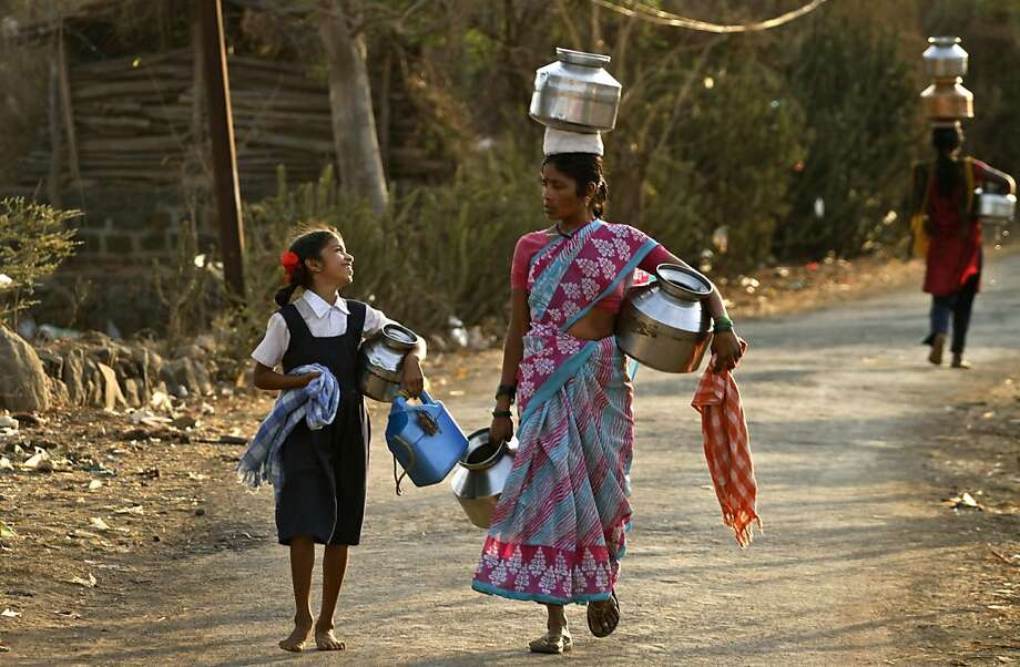 Indian villagers walk to fetch drinking water at Kasu village, in the western Indian state of Maharashtra. A lack of availability of drinking water in several villages compels village women to walk long distances to fetch water.  Photo: Rajesh Kumar Singh, Associated Press