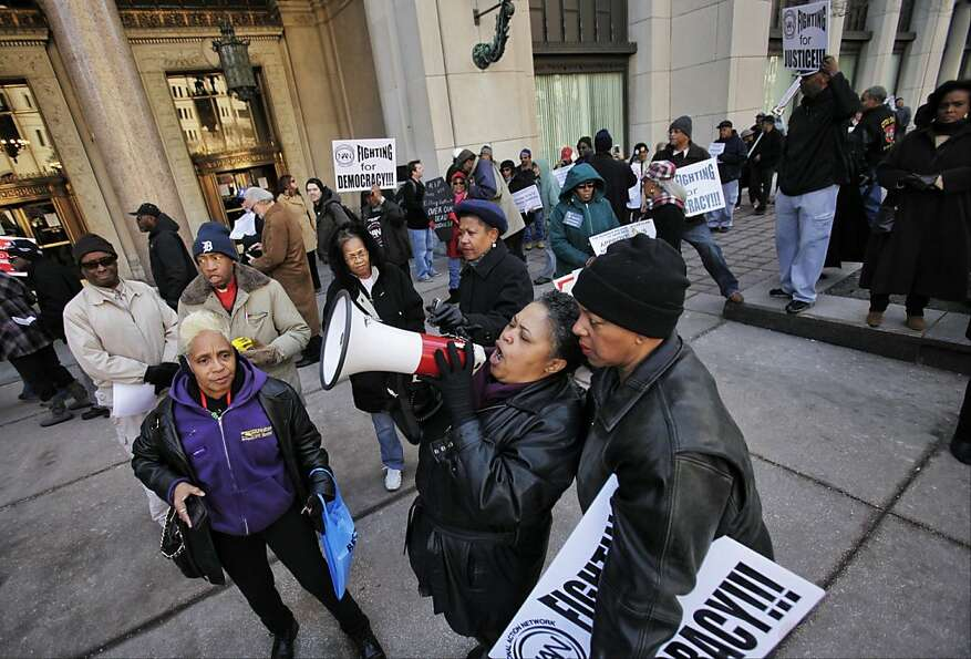 Protesters gather in front of the Cadillac Square building in Detroit to march and speak out against