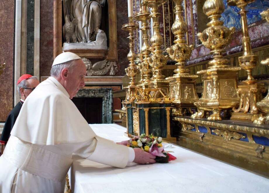 In this photo provided by the Vatican newspaper L'Osservatore Romano, Pope Francis puts flowers on the altar inside St. Mary Major Basilica, in Rome, Thursday, March 14, 2014. Pope Francis opened his first morning as pontiff by praying Thursday at Rome's main basilica dedicated to the Virgin Mary, a day after cardinals elected him the first pope from the Americas in a bid to revive a Catholic Church in crisis and give it a preacher with a humble touch. (AP Photo/L'Osservatore Romano, ho)