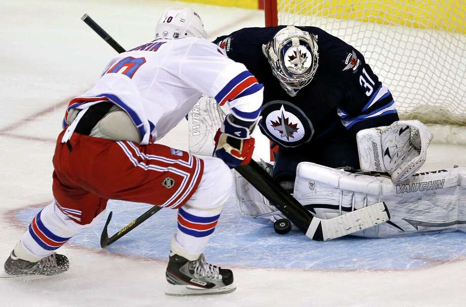 Winnipeg Jets goaltender Ondrej Pavelec (31) stops New York Rangers forward Marian Gaborik (10) on the penalty shot during the first period of their NHL hockey game, Thursday, March 14, 2013,in Winnipeg, Manitoba. (AP Photo/The Canadian Press, John Woods) Photo: John Woods