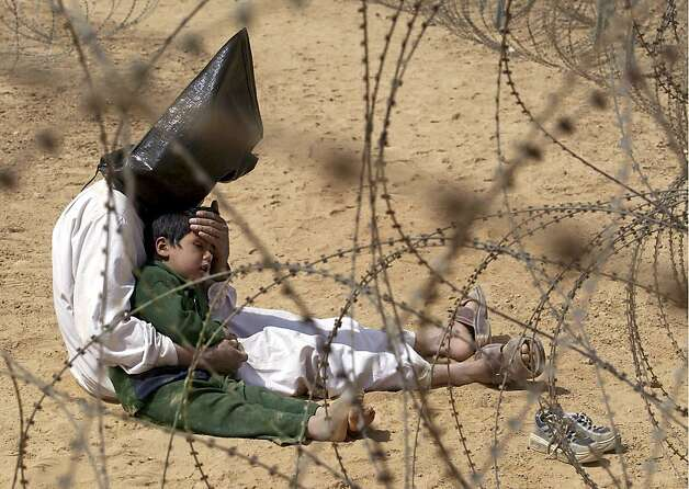 ** FOR USE AS DESIRED, PHOTOS OF THE DECADE ** FILE - An Iraqi prisoner of war conforts his 4-year-old son at a regroupment center for POWs of the 101st Airborne Division near An Najaf, in this March 31, 2003 file photo. The man was seized in An Najaf with his son and the U.S. military did not want to separate father and son. (AP Photo/Jean-Marc Bouju, File) Photo: Jean-marc Bouju, ASSOCIATED PRESS