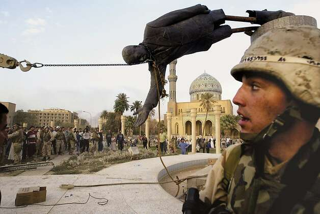 Iraqi civilians and U.S. troops pull down a statue of Saddam Hussein in Baghdad on April 9, 2003, shortly after the war began. Photo: Jerome Delay, ASSOCIATED PRESS
