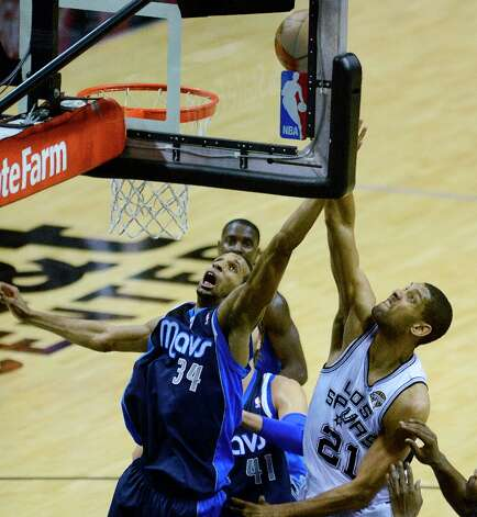 Tim Duncan of the Spurs (21) shoots over Brandan Wright (34) of the Dallas Mavericks at the AT&T Center on Thursday, March 14, 2013. Photo: Billy Calzada, San Antonio Express-News / San Antonio Express-News
