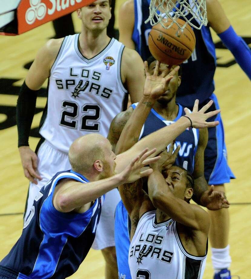 Kawhi Leonard of the Spurs is foiled by Chris Kaman of the Dallas Mavericks as he attempts to complete a layup at the AT&T Center on Thursday, March 14, 2013. Photo: Billy Calzada, San Antonio Express-News / San Antonio Express-News