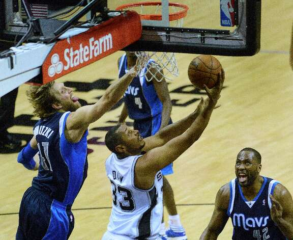 Boris Diaw of the Spurs scores on a reverse as Dirk Nowitzki (left) and Elton Brand (42) of the Dallas Mavericks defend at the AT&T Center on Thursday, March 14, 2013. Photo: Billy Calzada, San Antonio Express-News / San Antonio Express-News
