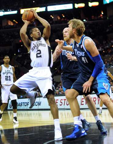 Kawhi Leonard of the Spurs shoots a fadeaway as Dirk Nowitzki (41) and Chris Kaman of the Dallas Mavericks defend during second-half NBA action at the AT&T Center on Thursday, March 14, 2013. Photo: Billy Calzada, San Antonio Express-News / San Antonio Express-News