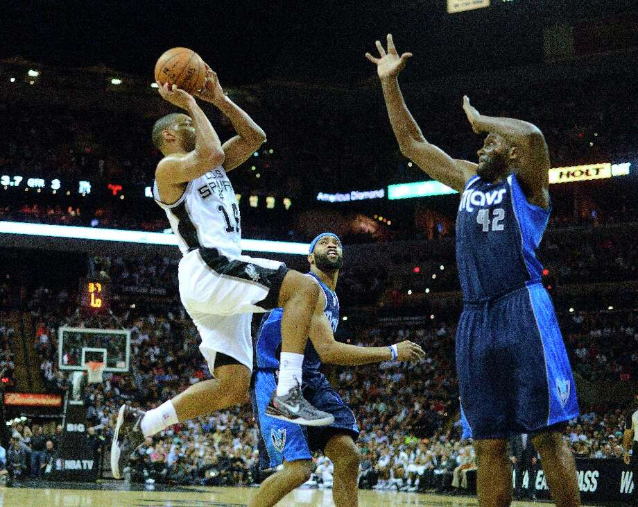 Gary Neal of the Spurs drives as Elton Brand of the Dallas Mavericks defends during second-half action at the AT&T Center on Thursday, March 14, 2013. Photo: Billy Calzada, San Antonio Express-News / San Antonio Express-News