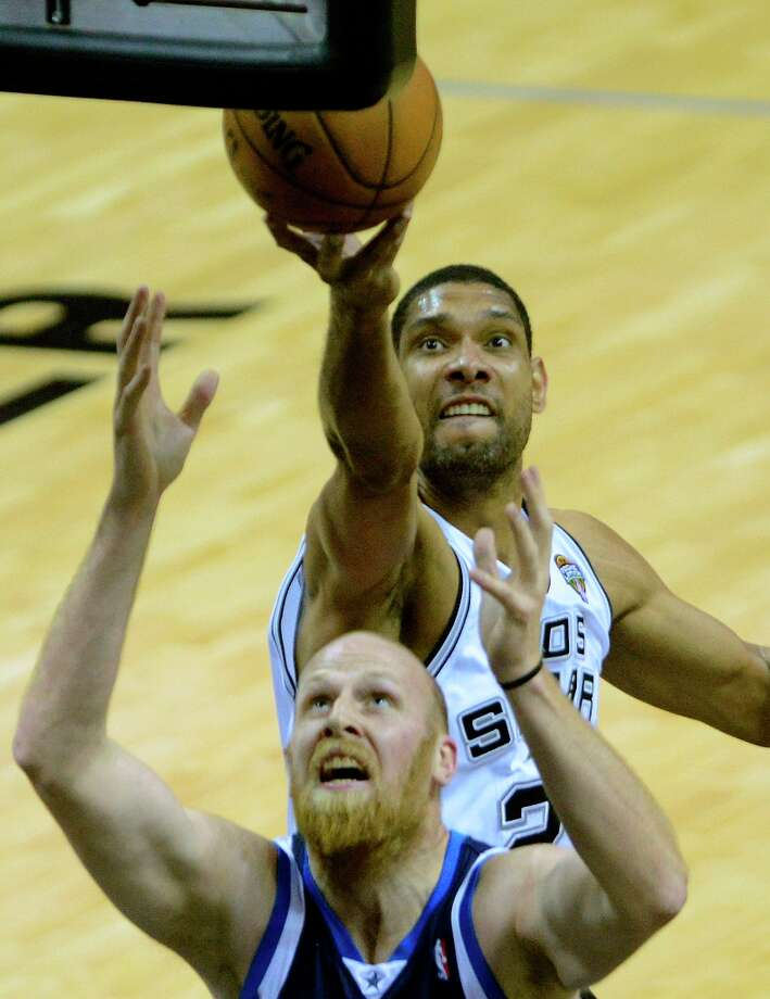 Tim Duncan of the Spurs rebounds over Chris Kaman of the Dallas Mavericks at the AT&T Center on Thursday, March 14, 2013. Photo: Billy Calzada, San Antonio Express-News / San Antonio Express-News