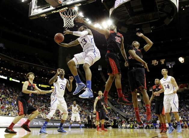 Kansas guard Ben McLemore (23) slips under the outstretched arm of Texas Tech forward Jordan Tolbert (32) to get to the basket during the second half. Photo: Charlie Riedel / Associated Press