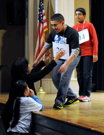 Abram Goda, 12, of Bridgeport, Conn., is congratulated by his mother Bahieh Jabboury, and sister Natilie Mikhaeel, 8, after winning the Hearst Media Services Spelling Bee, held at Western Connecticut State University in Danbury, Conn. Thursday, March 14, 2013. Photo: Carol Kaliff / The News-Times