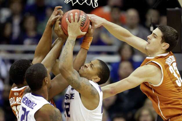 Kansas State guard Rodney McGruder (22) battles for a rebound with Texas forwards Jonathan Holmes (10) and Ioannis Papapetrou (33) during the first half of an NCAA college basketball game in the Big 12 tournament on Thursday, March 14, 2013, in Kansas City, Mo. Kansas State forward Jordan Henriquez (21) gets in on the play. (AP Photo/Orlin Wagner) Photo: Orlin Wagner, Associated Press / AP